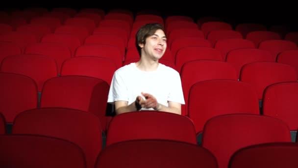 Mann sitzt allein und applaudiert in leerem Kinosaal oder Theater