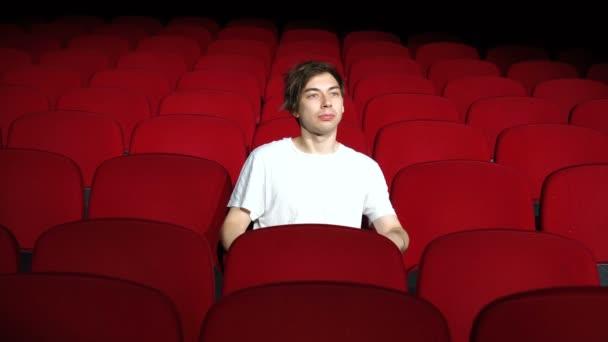 ember, aki egyedül ül az üres mozi csarnokban, és elégedetten