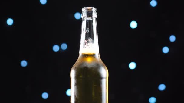 Nyitott sörösüveg közeli. Világos sör fekete háttéren elforgatva.