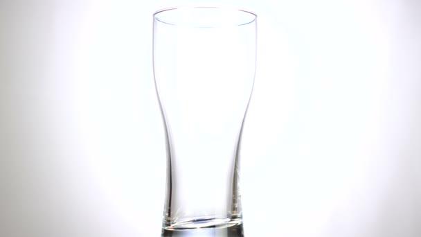 Prázdné sklo se pomalu otáčí kolem její osy. Zavřete 4k video. Bílé pozadí