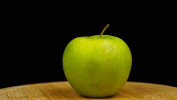 Zelené jablko na dřevěné desce, otáčení o 360 stupňů. Černé pozadí