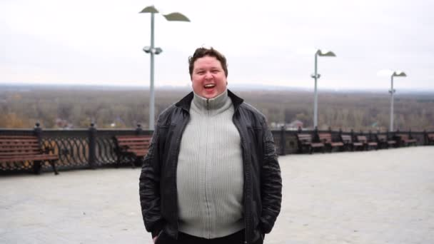 Zoom in from close up, portrait of happy fat man looking directly at camera and laughing