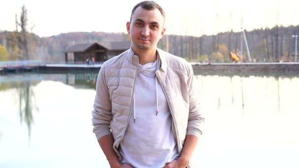 Portrét mladého pohledného muže v podzimním oblečení. Muž v bílém podzimním oblečení vypadá bez emocí do kamery