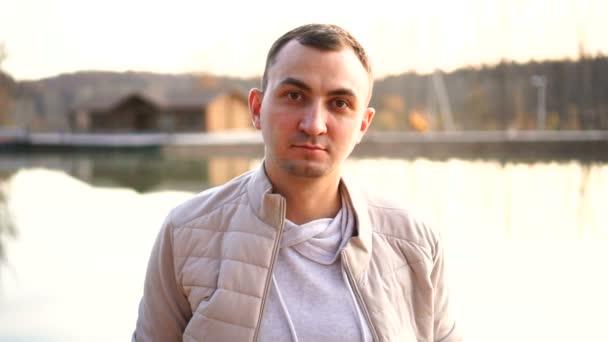 Porträt eines jungen, gut aussehenden Mannes in Herbstkleidung. Mann in weißer Herbstkleidung blickt emotionslos in die Kamera