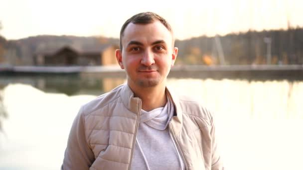 Portrét mladého pohledného muže v podzimním oblečení. Muž v bílém podzimním oblečení se dívá do kamery a usmívá