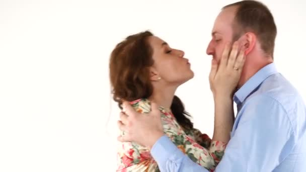 Happy newlyweds embracing, kissing and looking camera on white background
