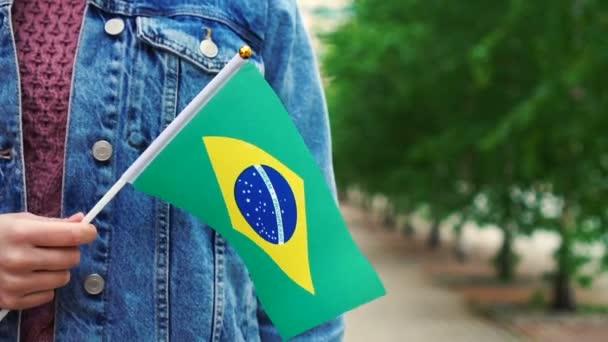 Zpomalený pohyb: Neznámá žena držící brazilskou vlajku. Dívka kráčí po ulici s národní vlajkou Brazílie