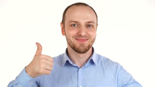 Hezký evropský muž se usmívá na kameru a drží palec nahoru.