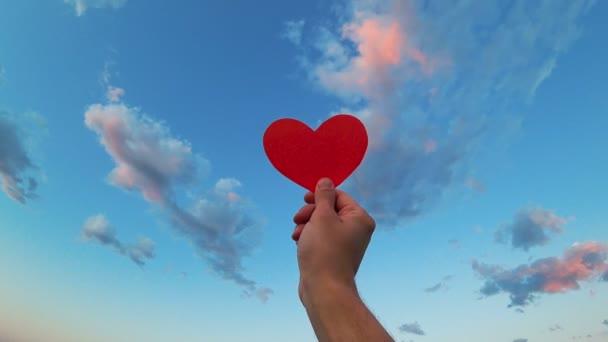 Ruka drží červený papír srdce na zamračené obloze pozadí