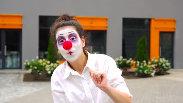 Mime Mädchen winkt mit der Hand. Schöne Clownin winkt Hallo