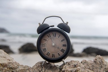 Alarm clock on a rock in the sunrise by the ocean