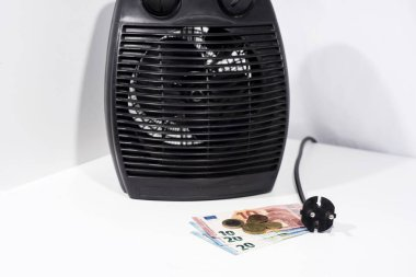 Money for heating bills with black heater on white background. Autumn season.