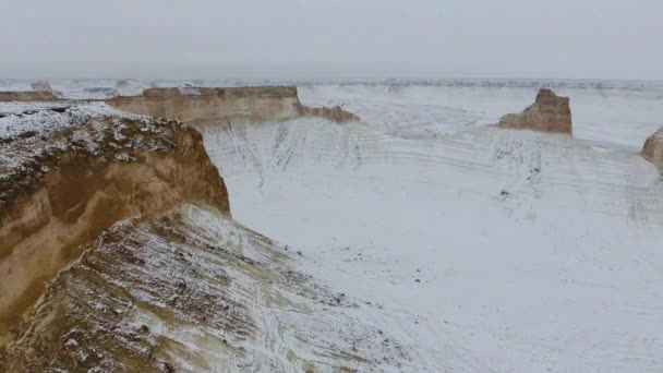 Amazing aerial view of snow-covering Ustyurt sandy mountains in Western Kazakhstan, Mangyshlak Peninsula. Desert in the snow.