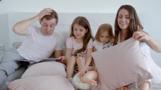 Happy family spending time in bedroom with children and reading book