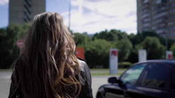 Záběr zezadu blondýna žena chůze k autu na parkovišti