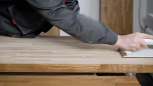 Carpenter je zpracování dřevěných prken, broušení brusným papírem, třením povrchu, detail rukou