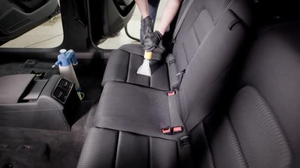 člověk je mytí sedadla automobilu, používající zvuková vysavač v čerpací stanici, profesionální čištění