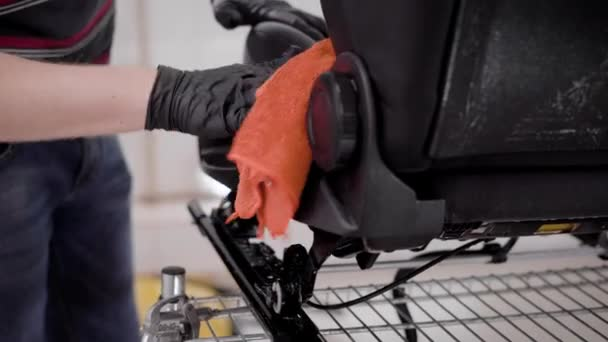 master is wiping auto seats and smearing fittings by oil in auto-service, cleaning of automobiles