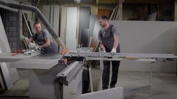 dva truhláři pracují v truhlářské dílny v závodě, řezání dřevotřískových desek pro přípravu pro výrobu nábytku
