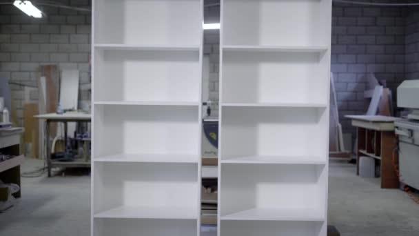 dvě bílé hotové skříně s policemi jsou stojící v dílně tesařství, vertikální panorama