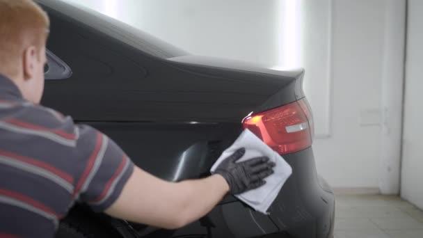 Zadní pohled na člověka pomocí ručníkem utírat zadní černé auto v garáži
