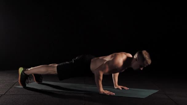 Muscular male athlete model doing pushups on a mat in a professional studio.