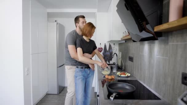 Woman cooking breakfast in the kitchen while her husband hugging her from behind.