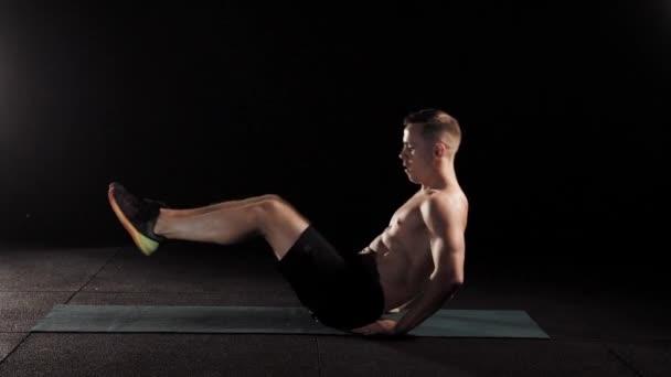mladý muž silný je trénink ve fitness centru, ležící na sportovní podložka, rostoucí nohy a trup od podlahy