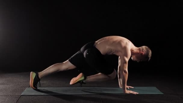 fiatal sportos férfi végez fizikai gyakorlatok a tornaterem, a sport szőnyeg működő izmok a láb