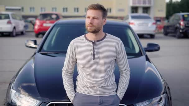 An attractive man with a beard stands next to his car in the parking lot. He is thoughtful, and looks away, someone is waiting