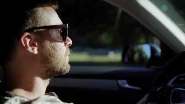 A man is driving a modern car. A handsome man with a beard in the sun protective glasses, confidently steers.