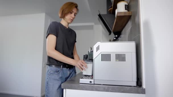 woman is putting container of milk in a coffee machine in home kitchen and switching it on in morning time
