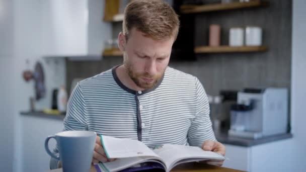 dospělý člověk odpočívá ve své kuchyni v víkendový den sám, obracející stránky časopisu a čtení článků