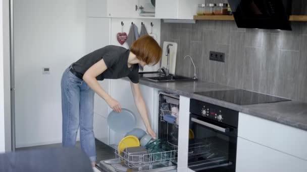 Frau lädt verschmutztes Geschirr in Spülmaschine