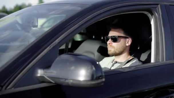 Stylish successful man driving a black luxury car in summer.