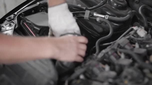 Detailní záběr profesionální automechanik Oprava části pod kapotou vozu, oprava vozu motor.