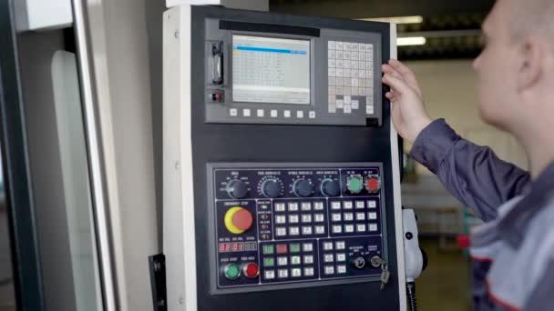 inženýr je programování cnc stroje ve výrobním provoze, stisknutím tlačítka a při pohledu na obrazovku