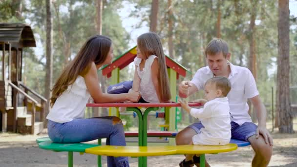 happy parents with their little children are resting on playground in park with high spruce in summer day