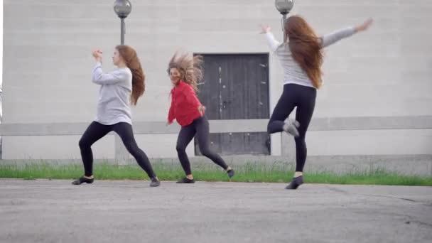 hot sale online bef94 13555 Drei hübsche junge moderne Ballerinas tanzen zeitgenössische Tänze auf  einer Straße, verschiedene Bewegungen durchführen