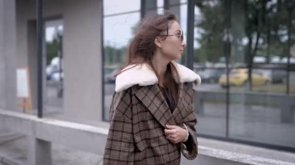 Venkovní portrét krásné módní dívka pózuje v ulici. Modelka se stylovém hnědém kabátě. Dámské modelevé koncept