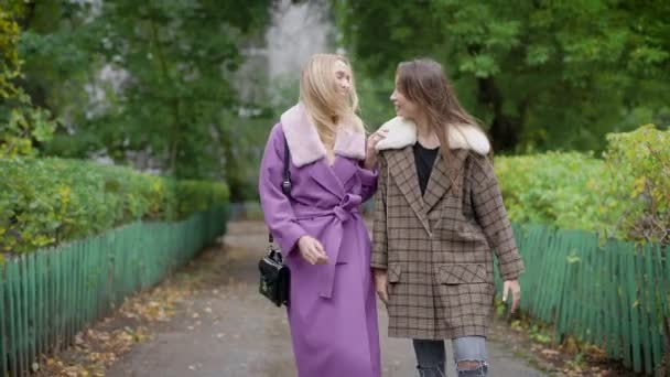 két vidám nő meg meleg kabátot visel a sikátorban a park és a beszélgető őszi nap gyaloglás