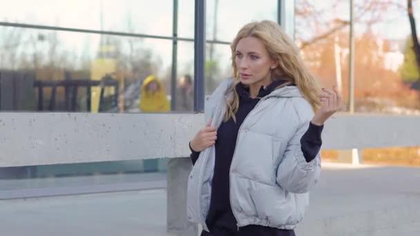 03f287f07efe Jolie femme se promenant dans la rue dans une doudoune de ville. Mode de  vie urbain– séquence vidéo