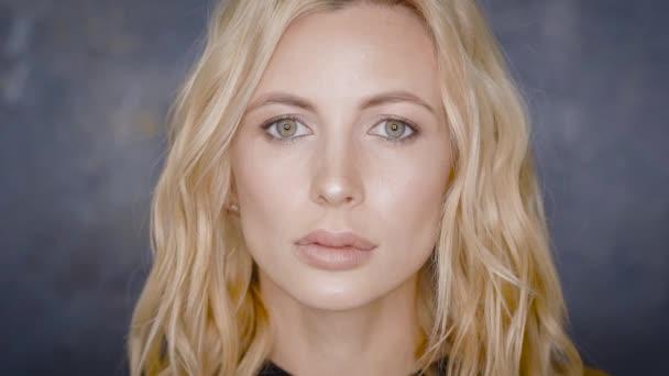 Detail portrét krásná blondýna s profesionální make-up, vystupují proti šedé stěny