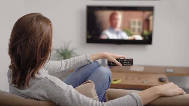 uvolněná žena sleduje filmy od televizní obrazovky ve svém domě, sedí na pohovce v obývacím pokoji v svátky