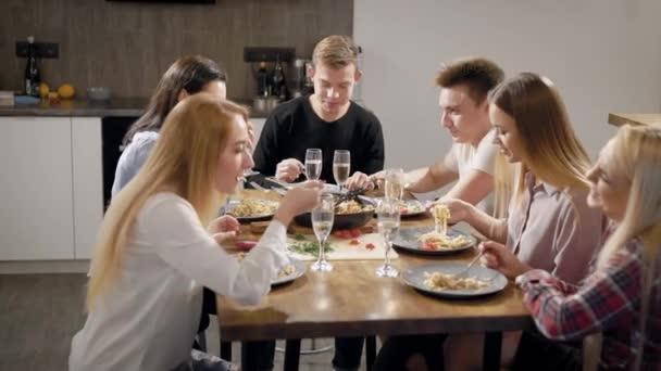 Skupina mladých spolubydlící sedí u stolu a jídelna, kliknutím u sklenky na víno říká toasty