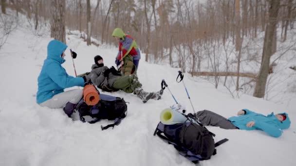 quattro persone riposano durante il trekking invernale nella foresta, sdraiati sulla neve e controllando Zaini