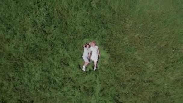 Colpo aereo. Vista epica dallalto, su due giovani donne sdraiate nellerba.
