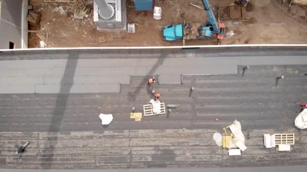 Dělníci na staveništi. Proces hydroizolace střechy. S pomocí speciálního materiálu je střecha zakrytá. Práce