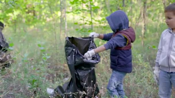 Skupina žen a dětí sbírá odpadky v lese. Dobrovolníci sbírají plastové a jiné odpady v černých plastových sáčcích. Za životní prostředí jsou odpovědni lidé.