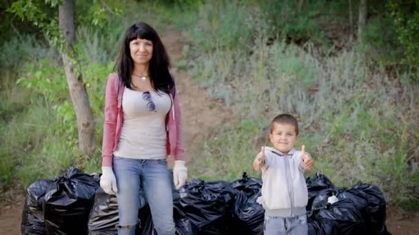 Matka ukazuje svůj příklad svému synovi, že je důležité vyčistit odpadky v lese. Environmentální vzdělávání je dáno rodiči.